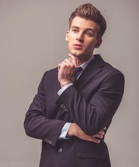 O homem de negócios pensativo considerável no terno está olhando afastado.