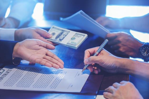 O homem de negócios põe a assinatura no contrato na reunião de negócios e em passar o dinheiro após negociações com os sócios comerciais.