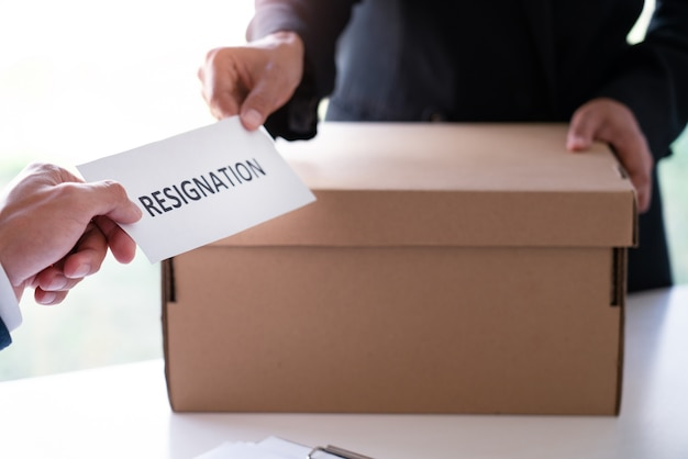 O homem de negócios que envia a carta de demissão ao chefe do empregador executivo na mesa a fim de renunciar dispensa o contrato, a colocação de emprego e o conceito de vagas.