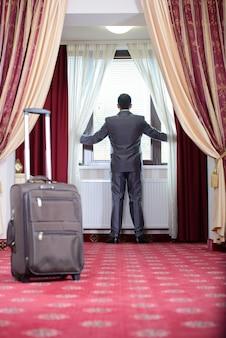 O homem de negócios que está na janela, apenas vai ao quarto de hotel.