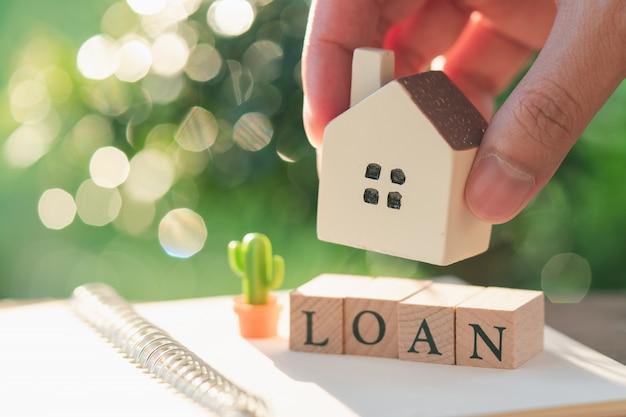 O homem de negócios que guarda um modelo modelo da casa é colocado na palavra de madeira empréstimo.