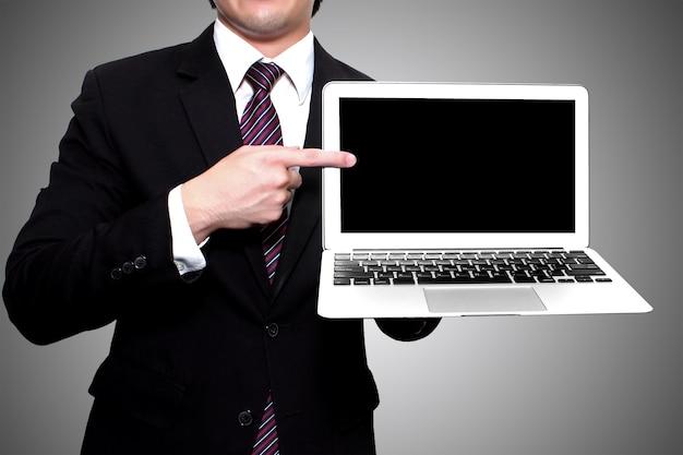 O homem de negócios que mostra o portátil