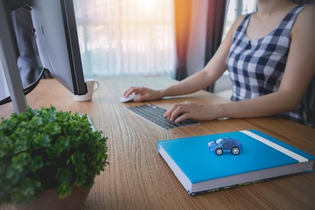 O homem de negócios que usa o computador para o aluguel, compra um carro com internet em linha.