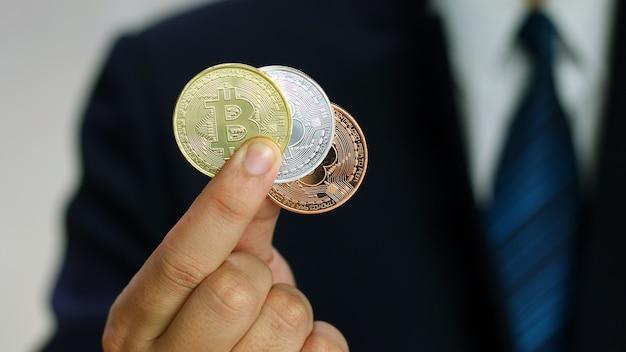 O homem de negócios que veste um terno está mostrando bitcoins em sua mão.