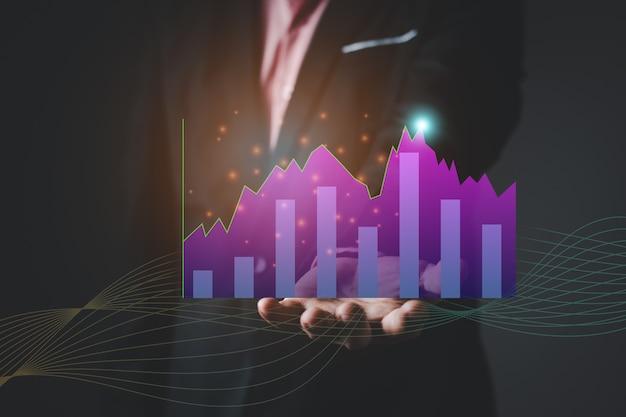 O homem de negócios segurando o gráfico econômico