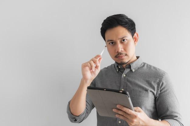 O homem de negócios sério e pensando do empresário trabalha em sua tabuleta com fundo cinzento.