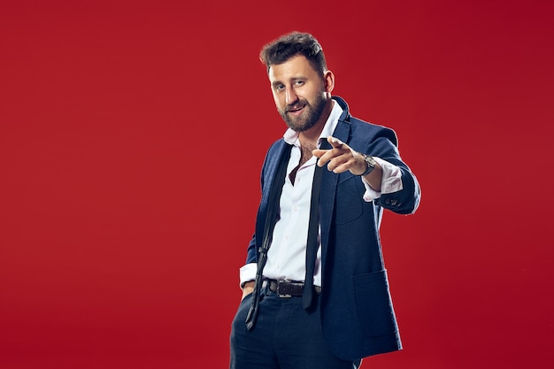 O homem de negócios sorridente aponta você, quero você, retrato de closeup de metade do comprimento no fundo vermelho do estúdio.