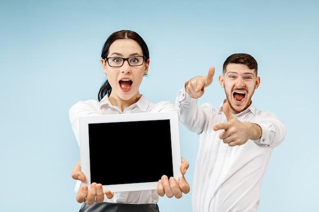 O homem de negócios surpreso e a mulher sorrindo em um estúdio azul