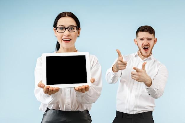 O homem de negócios surpreso e a mulher sorrindo em um fundo azul do estúdio e mostrando a tela vazia de um laptop ou tablet