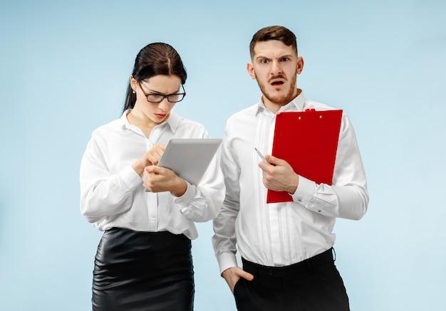 O homem de negócios surpreso e a mulher sorrindo em uma parede azul