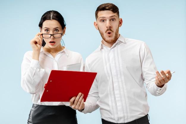 O homem de negócios surpreso e a mulher sorrindo na parede azul do estúdio