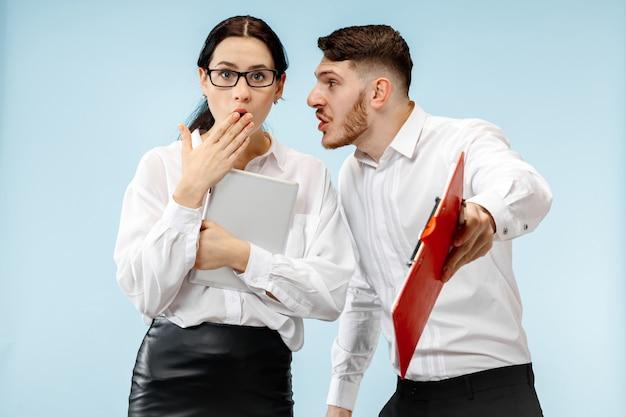 O homem de negócios surpreso e a mulher sorrindo sobre um fundo azul do estúdio