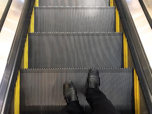 O homem de negócios vestiu as sapatas de couro pretas que estão na escada rolante. descer o elevador.