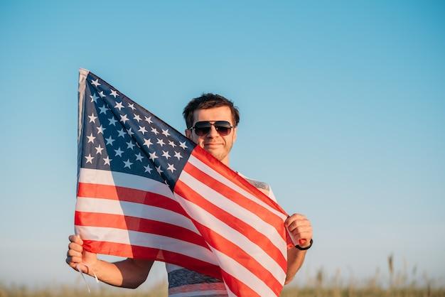 O homem de óculos de sol mantém a bandeira americana contra o céu azul. símbolo do dia da independência, 4 de julho nos eua
