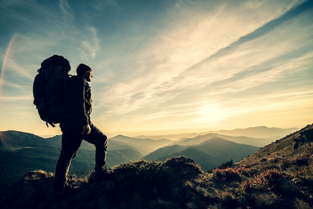 O homem de pé com uma mochila de camping em uma rocha com um pôr do sol pitoresco