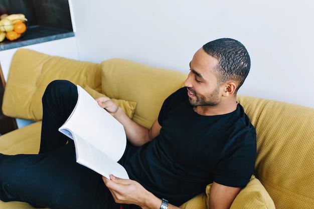 O homem de pele escura está descansando no sofá depois do trabalho. cara bonito com uma roupa de casa com interesse em ler uma revista. conforto, tempo livre, aconchego, relaxamento.