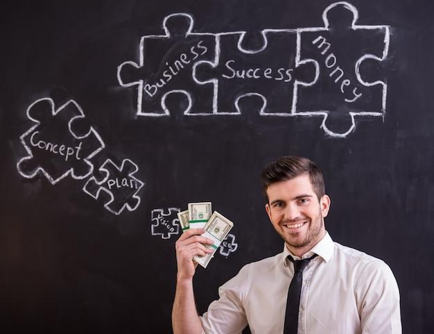 O homem de sorriso está guardando o dinheiro e está procurando ideias novas.