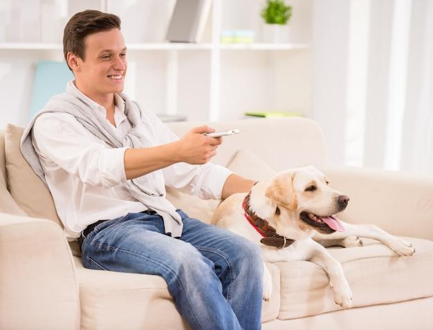 O homem de sorriso está sentando-se no sofá com cão e está olhando a tevê.