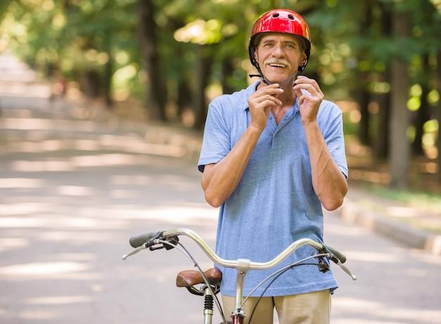 O homem de sorriso está vestindo o capacete ao sentar-se na bicicleta.