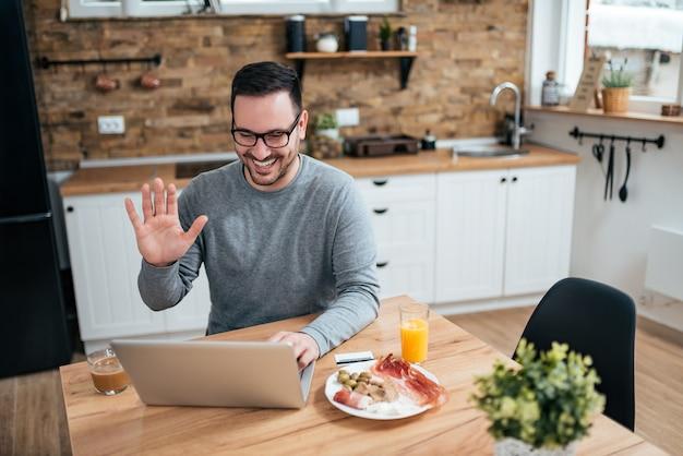O homem de sorriso que aprecia o café da manhã na cozinha e que tem um vídeo chama o portátil.