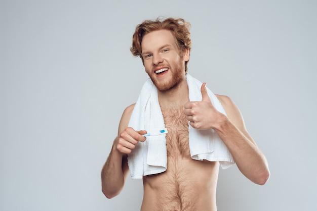 O homem de sorriso redheaded com escova de dentes está mostrando os polegares acima.