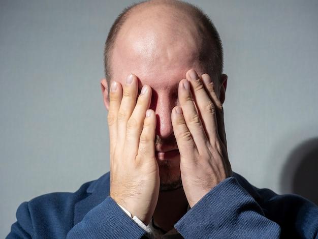 O homem de terno cobriu os olhos com as palmas das mãos. retrato de close-up. assustado, estalando, fechando os olhos para o que está acontecendo. emoção