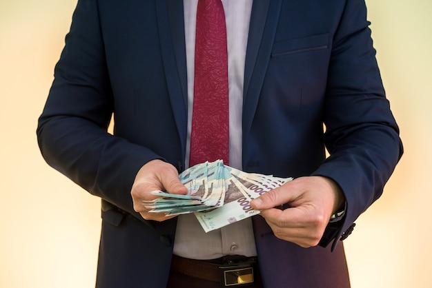O homem de terno conta os lucros. mãos masculinas convertem hryvnia