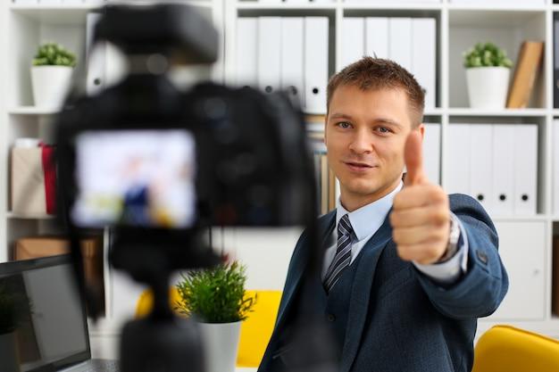 O homem de terno e gravata confirma o braço do sinal fazendo videoblog promocional ou sessão de fotos na câmera de vídeo de escritório para retrato de tripé.