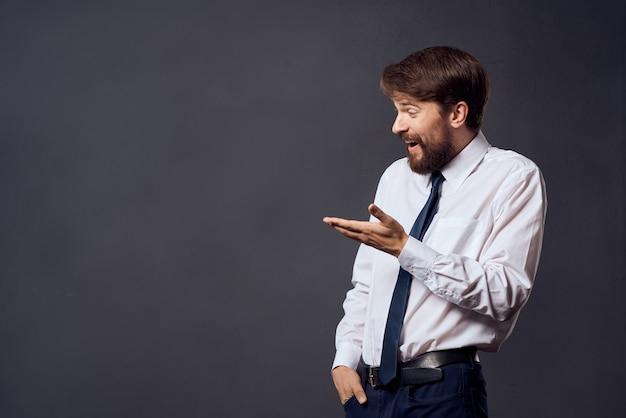 O homem de terno emoções gestos com as mãos fundo escuro