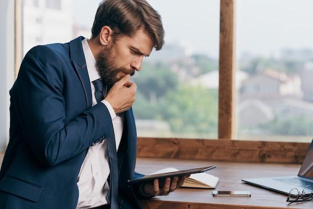 O homem de terno perto da janela com um laptop
