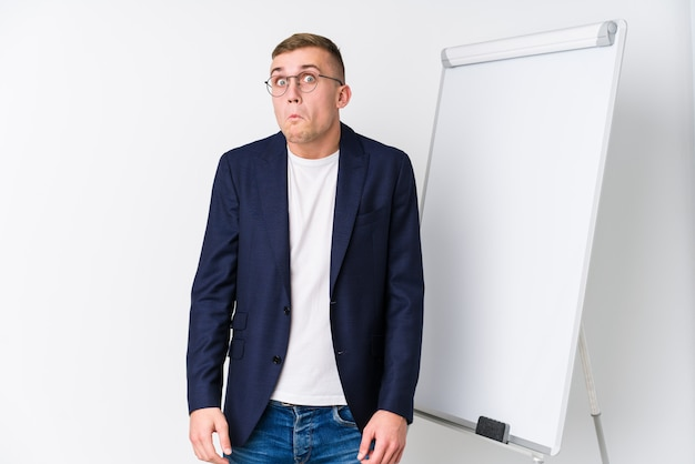 O homem de treinamento novo que mostra um quadro branco encolhe os ombros e abre os olhos confusos.