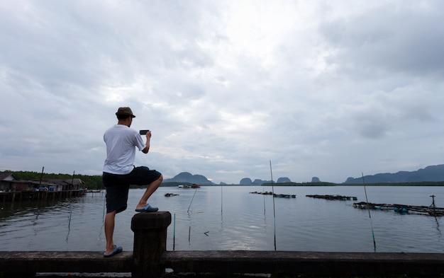 O homem de viagens em pé na ponte tira uma foto com o smartphone no nascer do sol da manhã.