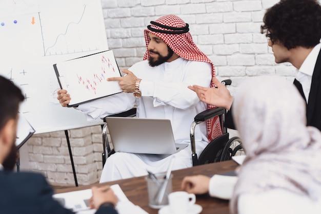 O homem deficiente mostra diagramas financeiros no escritório.