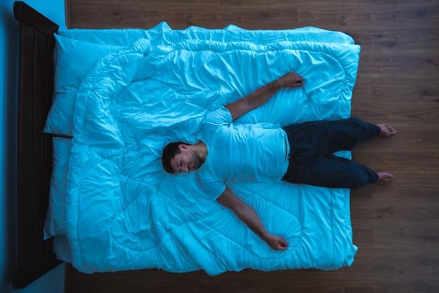 O homem deitado na cama. vista de cima, noite, noite