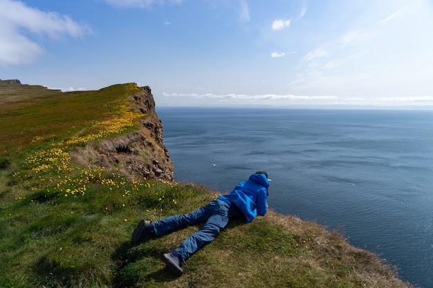 O homem deitado no penhasco latrabjarg e olhando para baixo.
