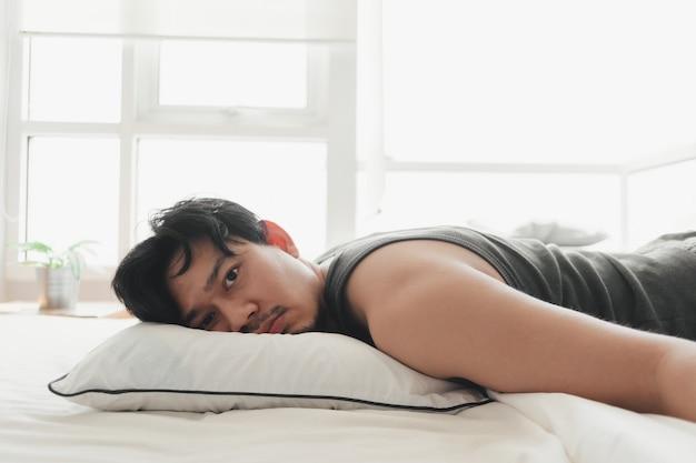 O homem deitou-se na confortável cama branca enquanto estava exausto.