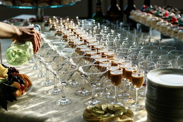 O homem derrama martini em copos de cocktail na mesa de jantar