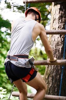 O homem desce na escada da corda