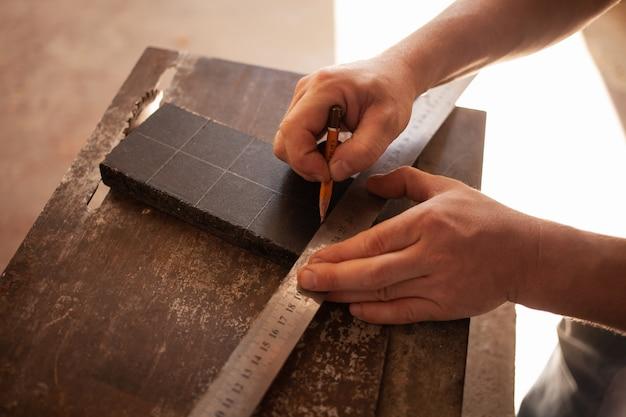 O homem desenha um lápis e uma régua em um pedaço de madeira para serrar. sutil