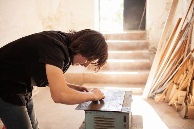 O homem desenha um lápis e uma régua em um pedaço de madeira para serrar.