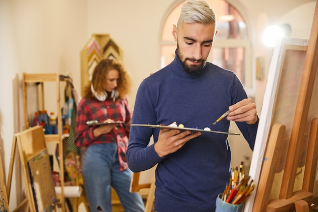 O homem desenha uma pintura no fundo de uma mulher também desenha uma pintura