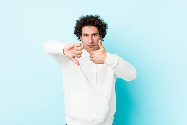 O homem desportivo novo contra um azul que mostra os polegares acima e os polegares para baixo, difícil escolhe o conceito
