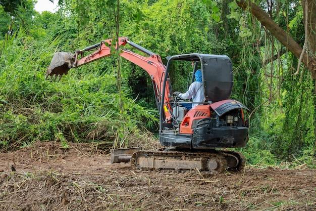 O homem dirige a retroescavadeira natureza clara para fazer a estrada do solo na tailândia