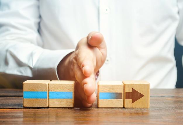 O homem divide os blocos de flecha em duas partes. interrupção do processo, diminuição da atividade