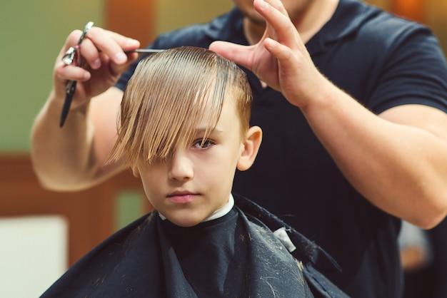 O homem do barbeiro faz o penteado bonito da moda para o menino em uma barbearia moderna