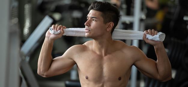 O homem do bodybuilder relaxa após ter levantado pesos no gym do esporte, fim acima.