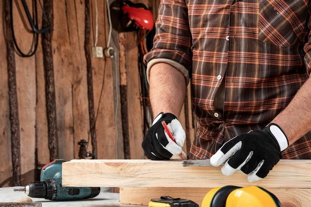 O homem do carpinteiro observa com um lápis nas marcas da placa para cortar, mãos masculinas com um close do lápis em uma placa de madeira. carpintaria