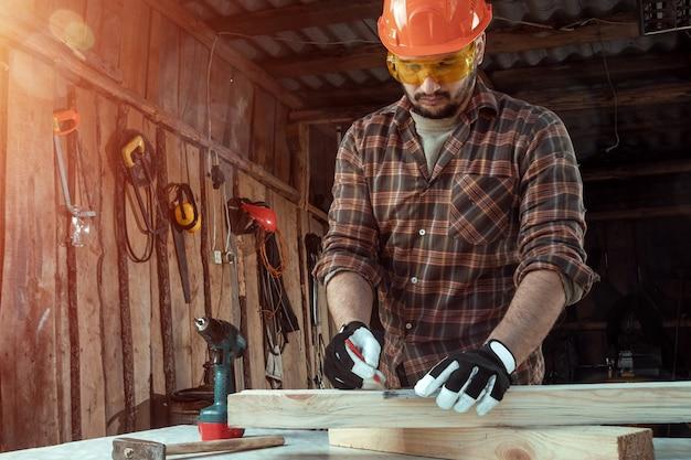 O homem do carpinteiro observa com um lápis nas marcas da placa para cortar, mãos masculinas com um close do lápis em uma placa de madeira.