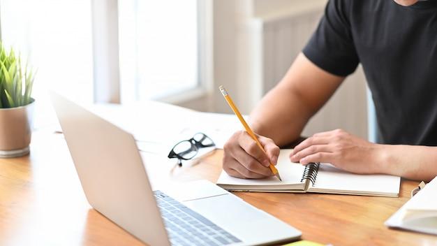 O homem do close-up escreve no portátil do papel do caderno.