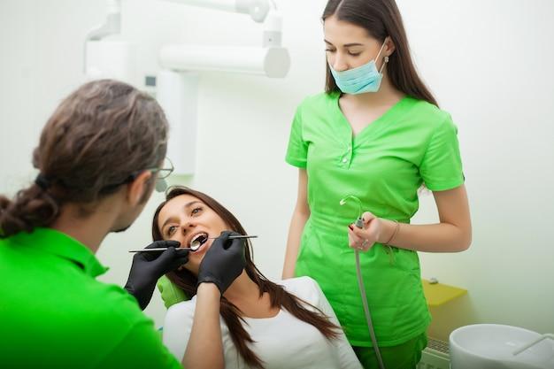 O homem do dentista está tratando os dentes ao cliente na clínica odontológica